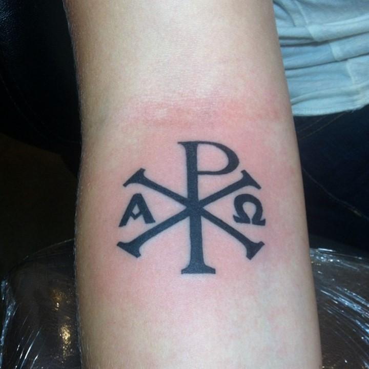 Religious forearm tattoo of Christ monogram Chi Rho in dark black ink