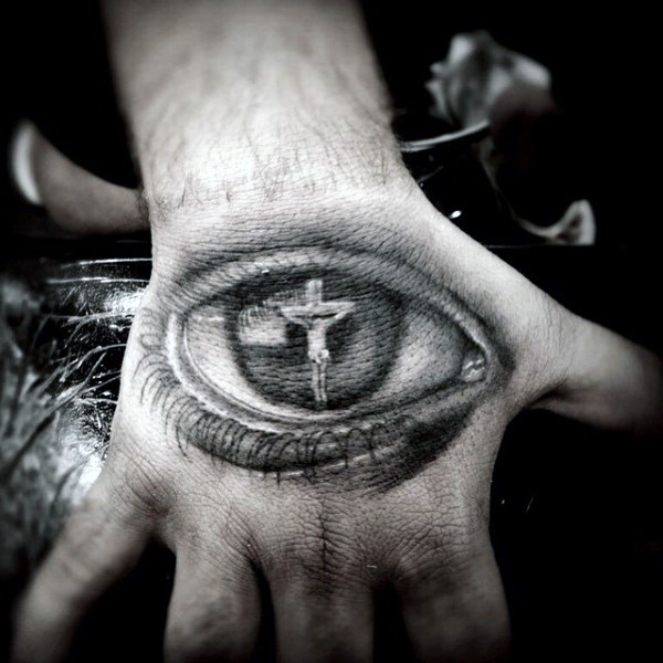 Religious Jesus Christ crucifix in human eye detailed tattoo on hand