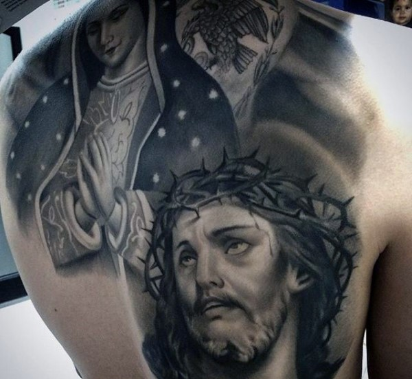 Religious style black and white back tattoo of Jesus and praying woman