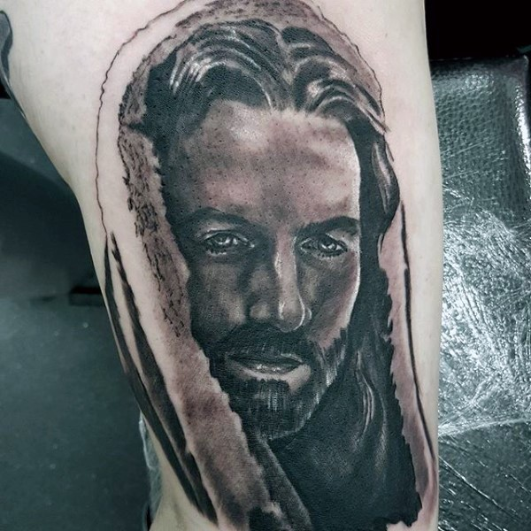 Religious style black and white thigh tattoo of Jesus portrait