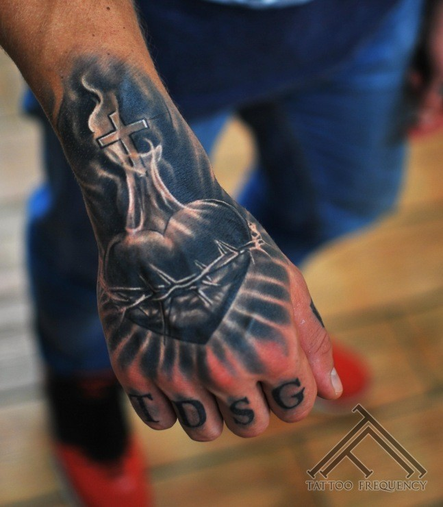 Religious theme colored hand tattoo of heart with cross