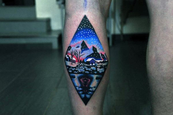Rhombus shaped colored small leg tattoo stylized with nigh countryside
