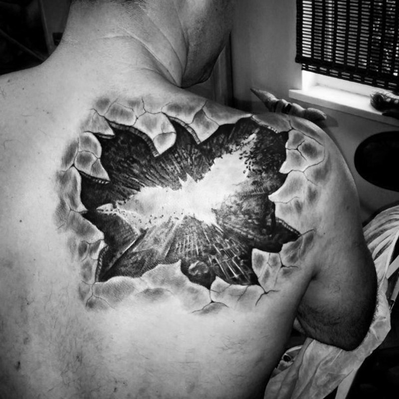 Ripped skin 3D like black and white Batman symbol tattoo on shoulder