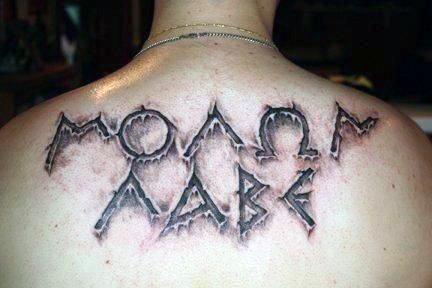 Ripped skin like black and white Latin warrior tattoo on upper back