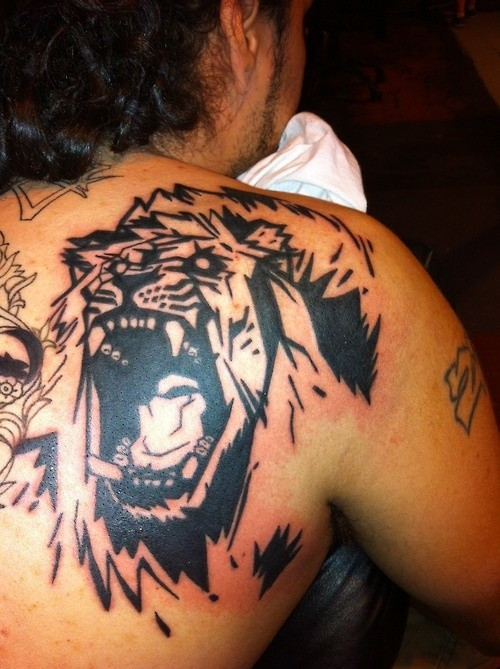 Roaring lion cartoonish tattoo on back