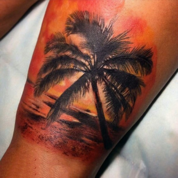 Romantic like colored ocean beach with palm tree tattoo on leg