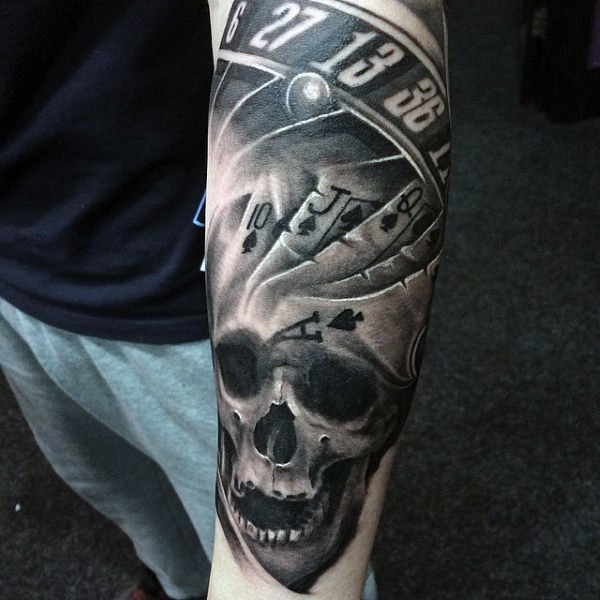Roulette, playing card and skull black and white gambling tattoo on arm