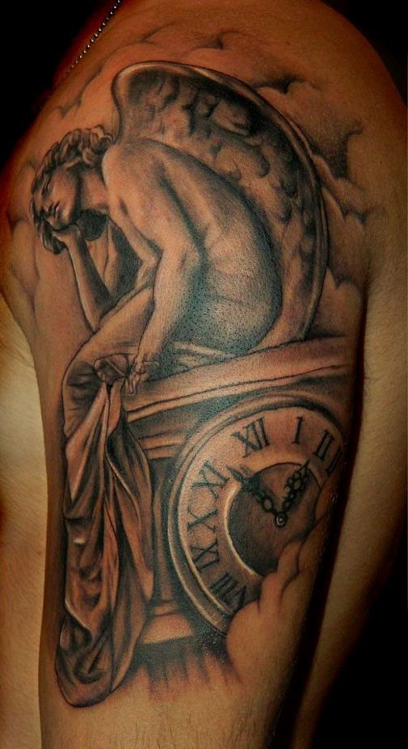 Sad angel and watches tattoo on shoulder