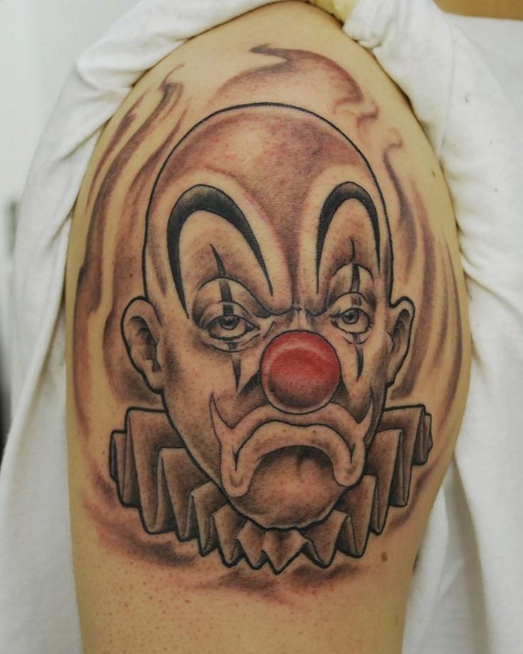 pagliaccio triste con naso rosso tatuaggio sulla spalla