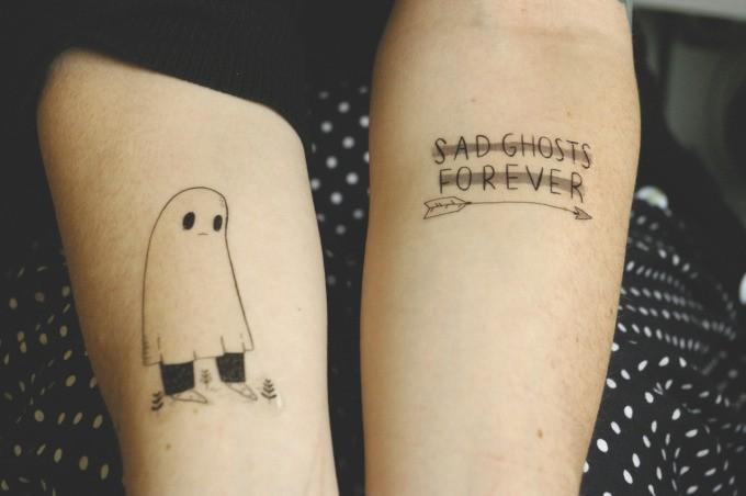 dolce e triste fantasma con frecca tatuaggio su due braccia