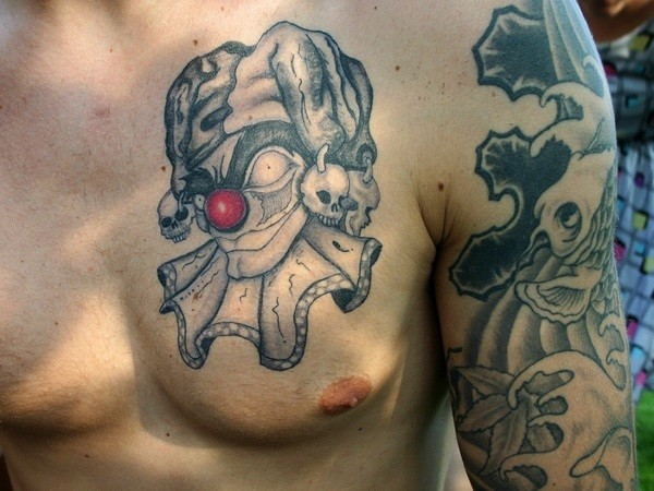Scary clown with red nose tattoo on chest