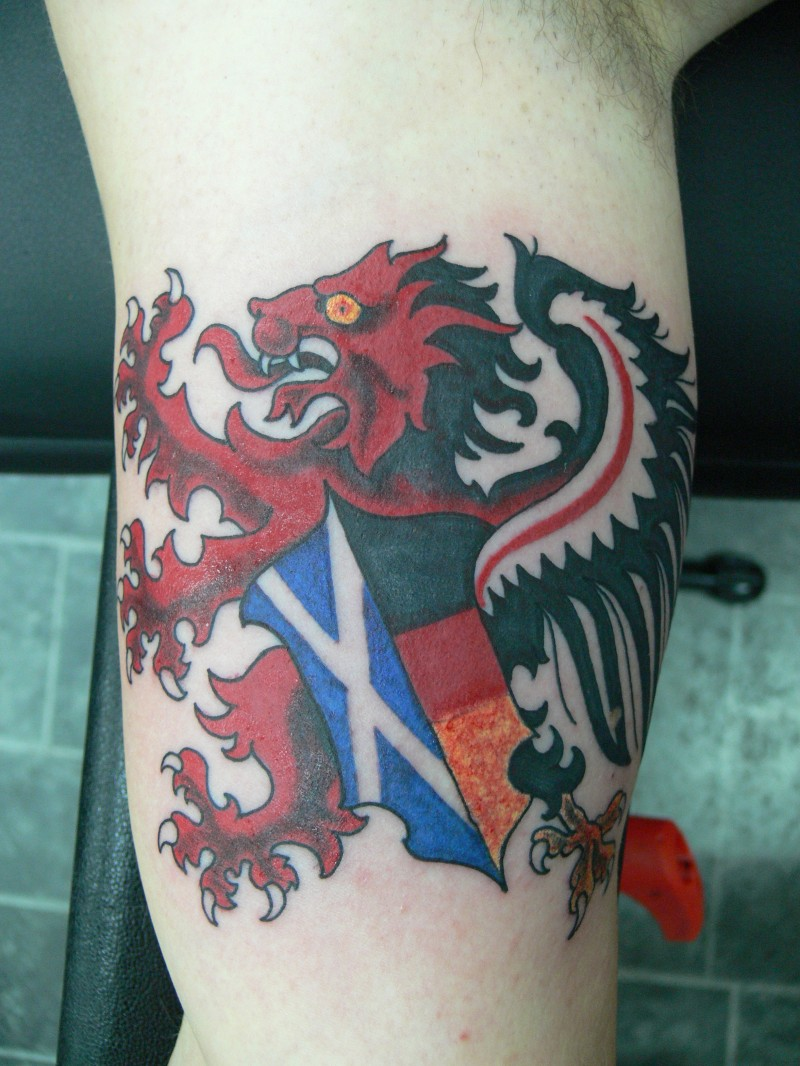 leone rosso con bandiera scozzese tatuaggio su braccio