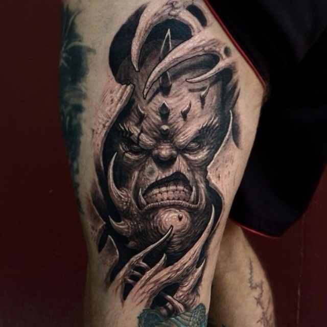 Sharp 3D style black and white thigh tattoo of demonic monster face