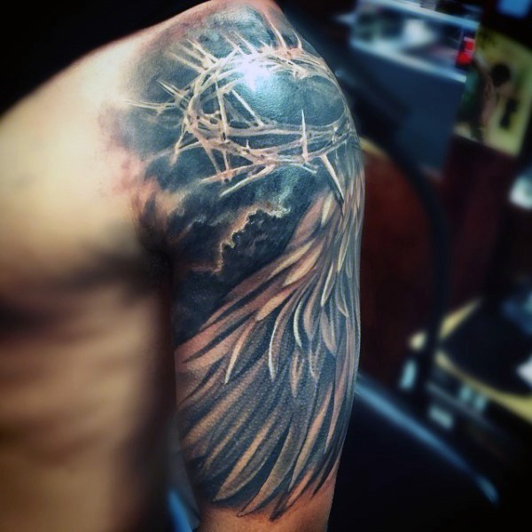 Sharp crown of thorns and feather wing religious shoulder tattoo in realistic style