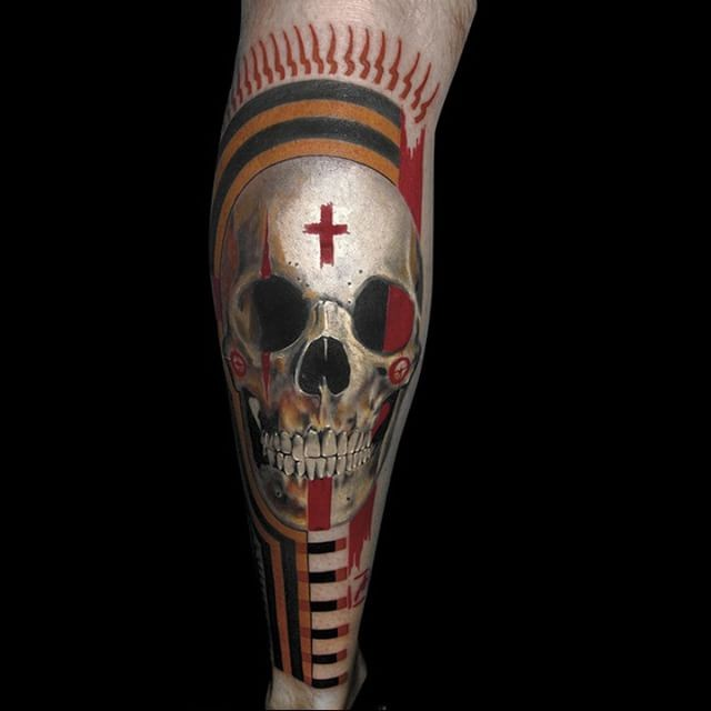 Sharp designed and colored leg tattoo of human skull and red cross