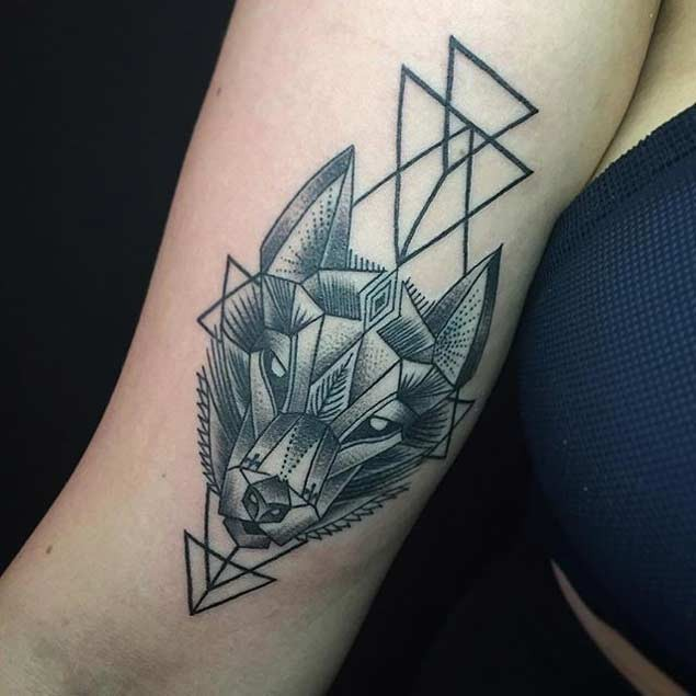 Sharp engraving style black ink wolf head tattoo on arm combined with black triangles