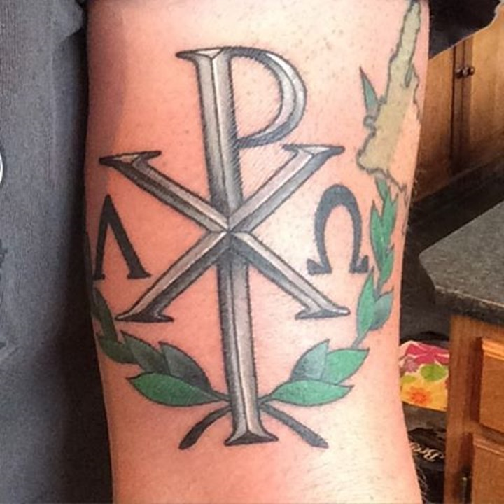 Silver Chi Rho special Christ monogram symbol in Laurel wreath colored tattoo on forearm