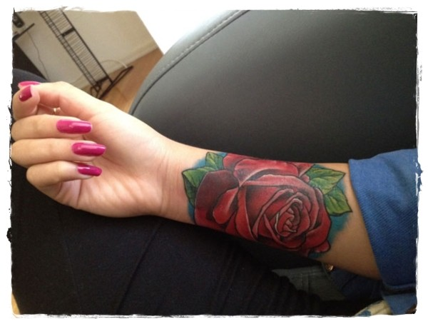 Simple big red colored rose tattoo on arm