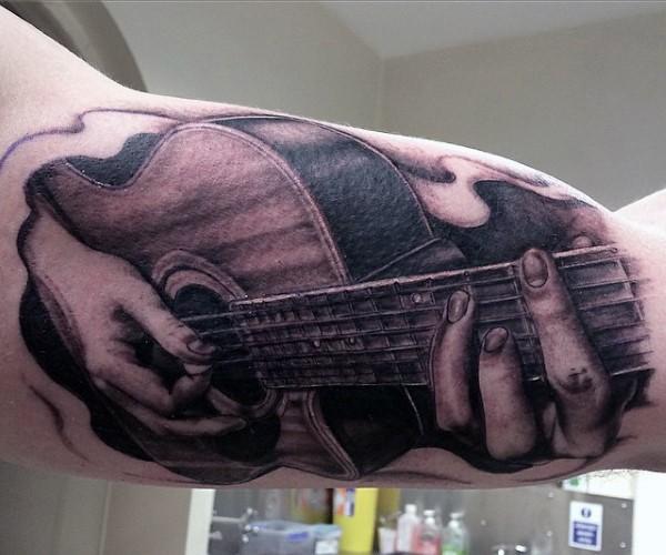 Tatuaje en el brazo, manos tiernos con guitarra acústica