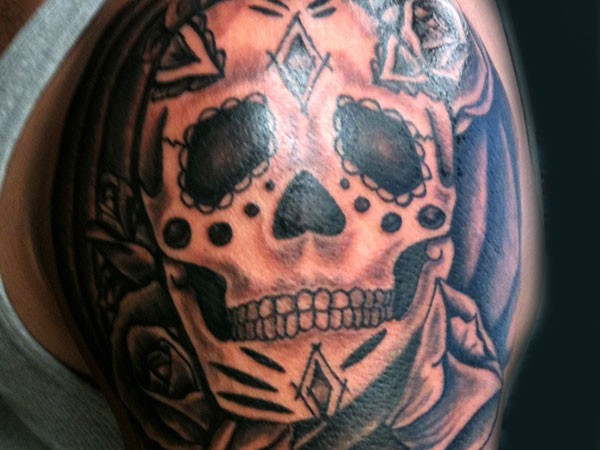 Simple black and white shoulder tattoo of human skull with flowers