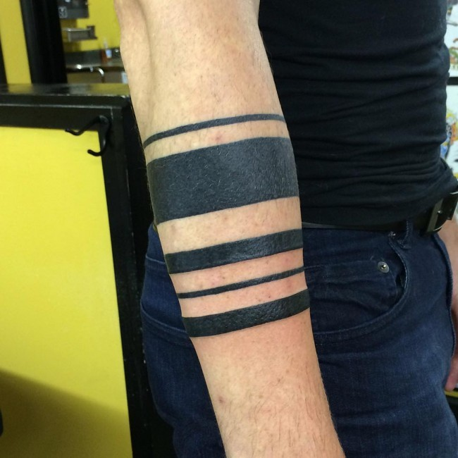 Simple black ink arm tattoo of different straight lines
