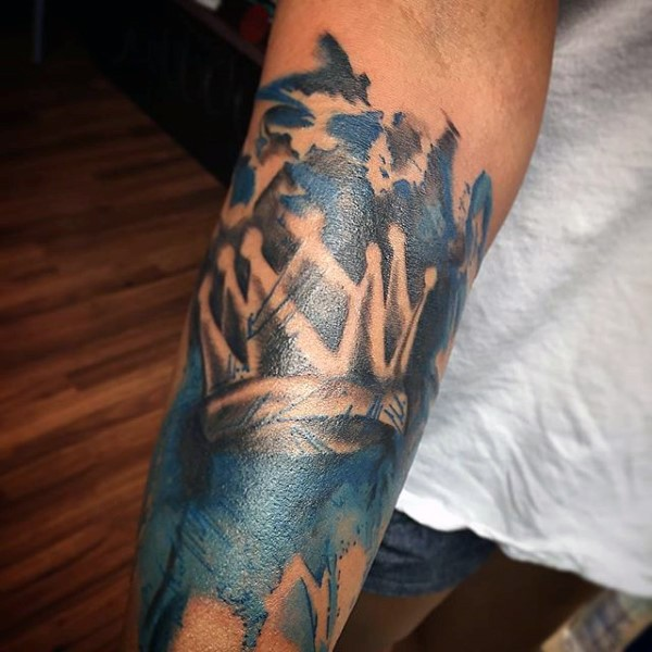 Tatuaje en el antebrazo, corona de rey en el fondo azul