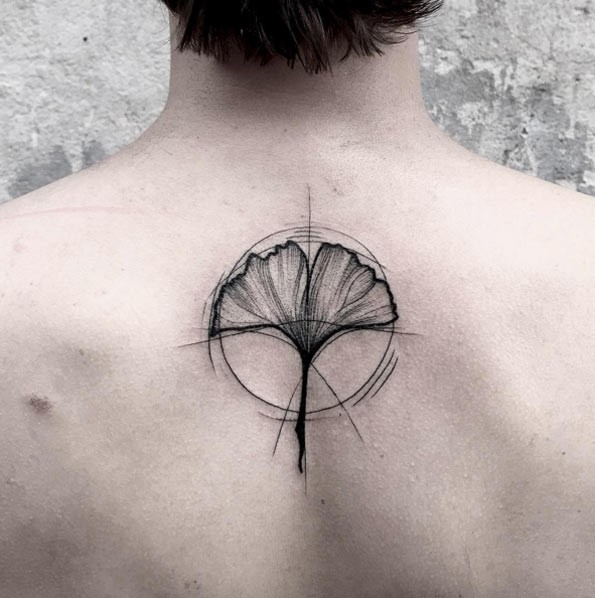 2d30bca96 Simple black ink flower shaped black ink tattoo on upper back with circle
