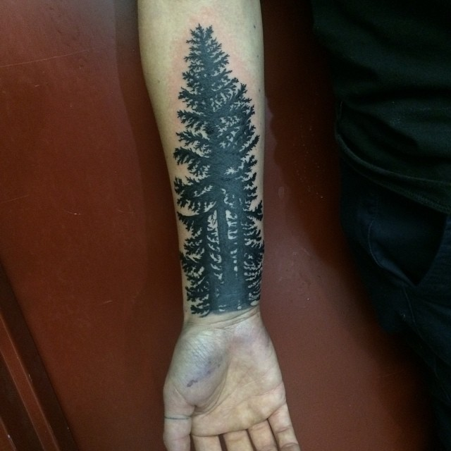 Simple black ink forearm tattoo of dark forest