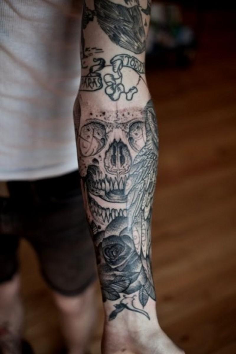 Tatuaje en el brazo, cráneo con alas y rosa, diseño precioso