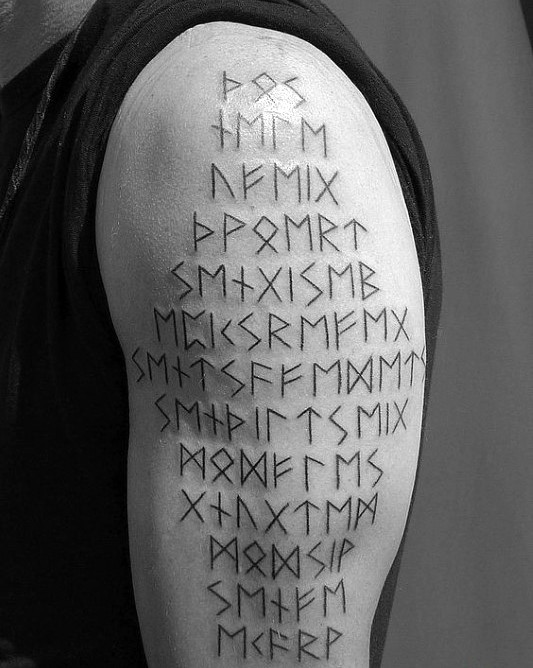 Simple black ink shoulder tattoo of ancient lettering