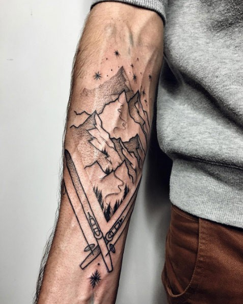 Simple blackwork style forearm tattoo of winter mountains with skii