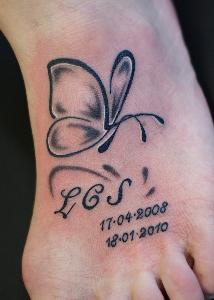 Simple butterfly tattoo with lettering and numbers