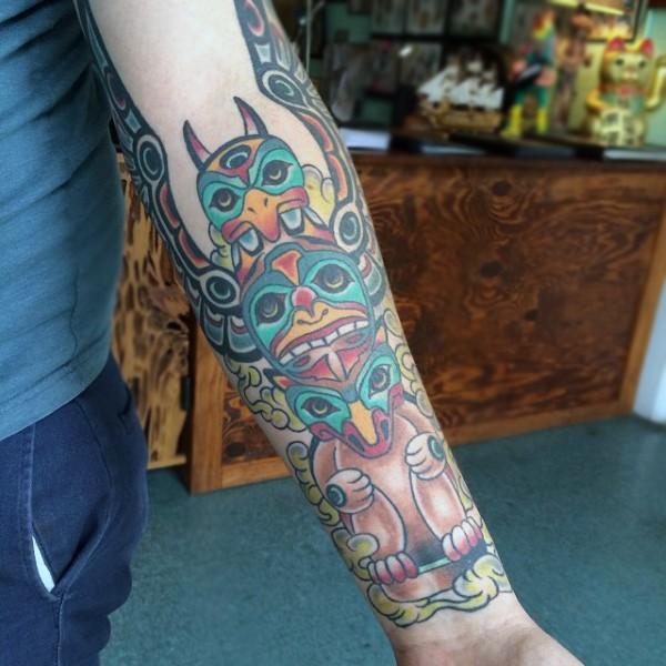 Simple cartoon like colored tribal statue tattoo on arm