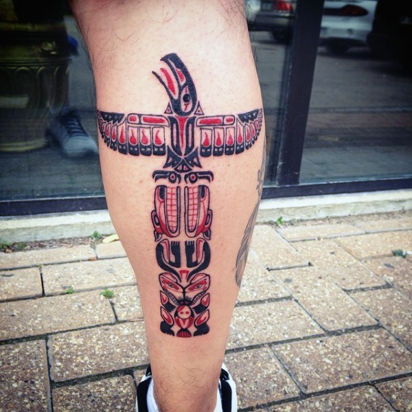 Simple designed and colored big tribal statue tattoo on leg