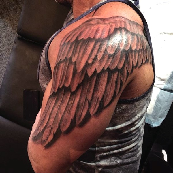 Simple designed and painted black and white wing shoulder tattoo