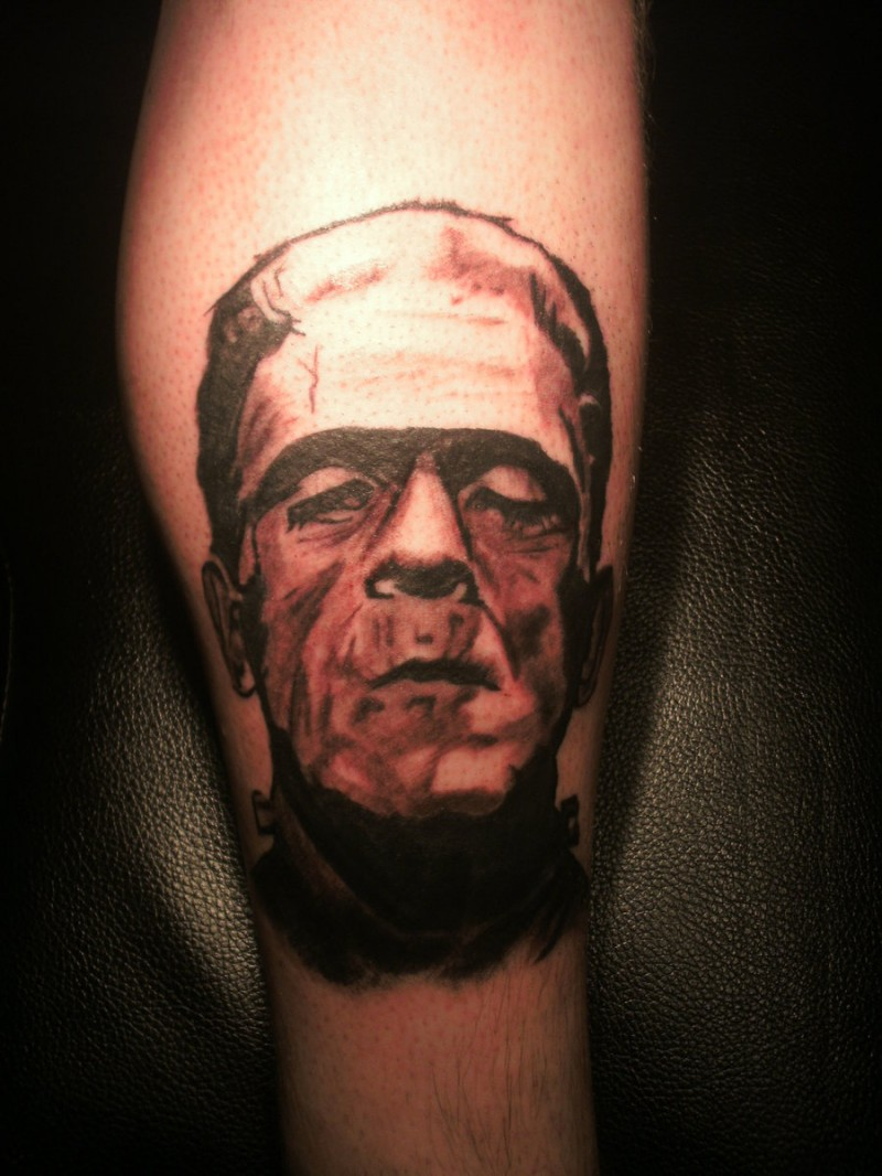 Simple designed black and white Frankenstein monster portrait tattoo on leg