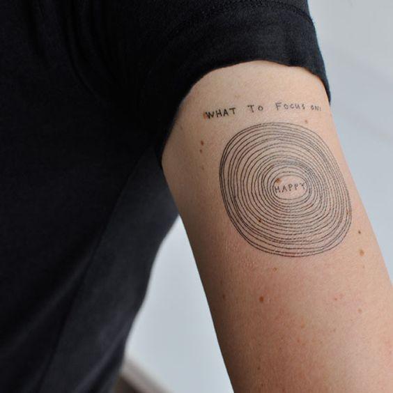 Tatuaje  de círculos simples con escrito en el brazo