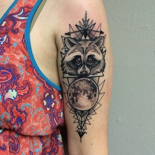 Simple homemade black ink raccoon tattoo on shoulder stylized with geometrical ornamnets