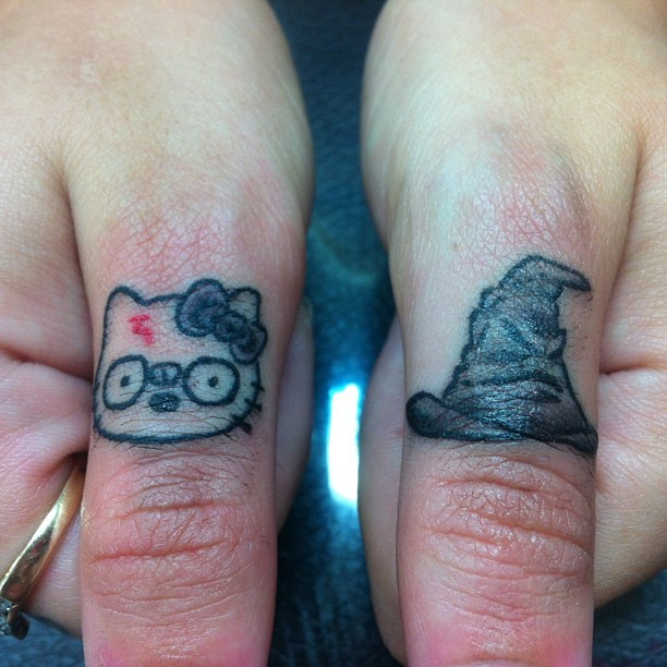 Simple homemade colored on finger tattoo of little cat and magical hat