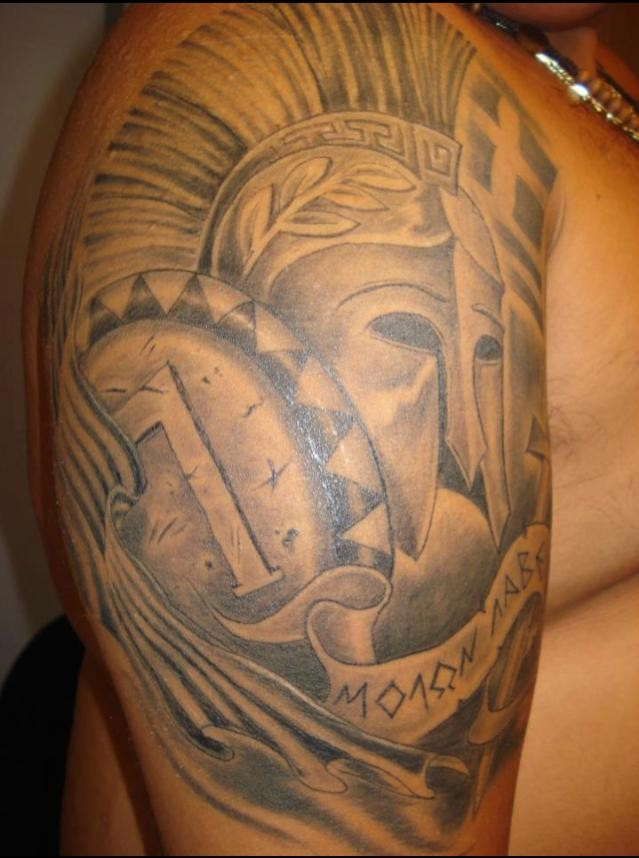 Simple homemade like black ink antic warriors armor tattoo on shoulder with lettering