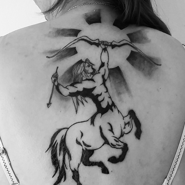 Simple homemade like black ink Sagittarius tattoo on back