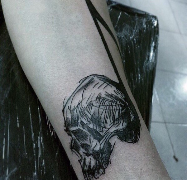 Simple homemade like black ink skull with note tattoo on arm