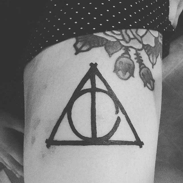 Simple homemade like black ink tattoo on triangle with circle