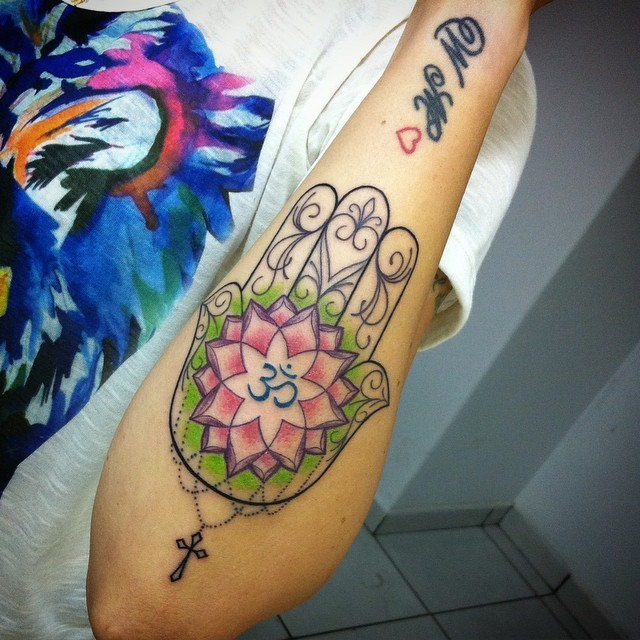 Simple homemade like colored Hamesh hand with symbol tattoo on forearm combined with tiny black cross
