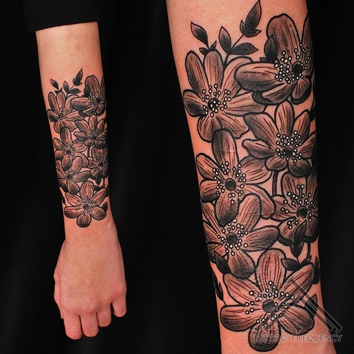 Simple illustrative style arm tattoo of big flowers with leaves