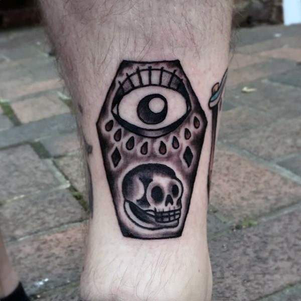 Simple little black and white coffin with skull and eye tattoo on leg