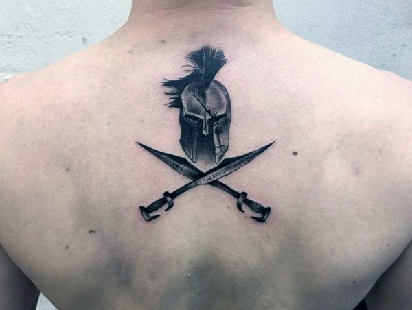 Simple little black ink Spartan helmet and crossed swords tattoo with lettering on upper back