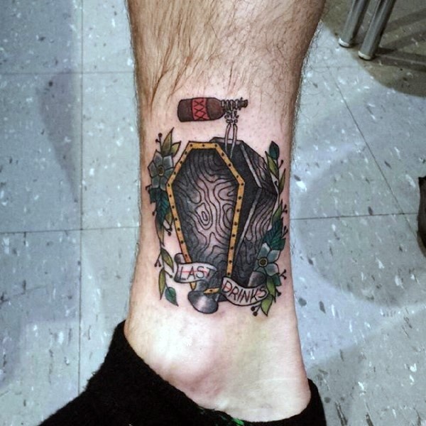 Simple little colored coffin with skeleton arm ad lettering tattoo on ankle
