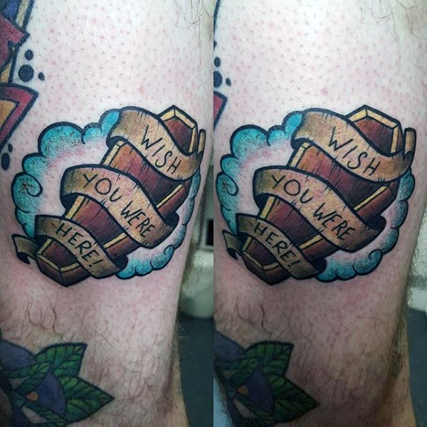 Simple little colored wooden coffin with lettering and ribbon tattoo on thigh