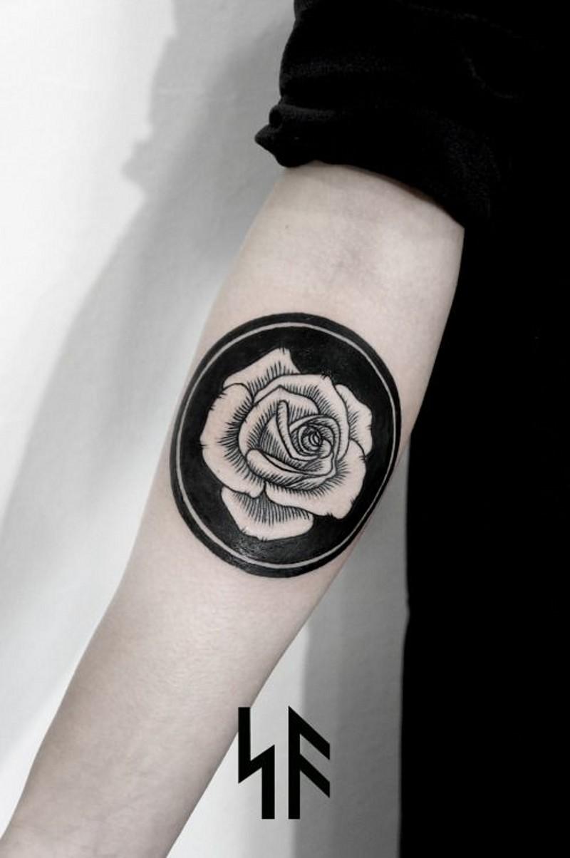 semplice piccolo rosa bianca in cerchio nero tatuaggio su braccio